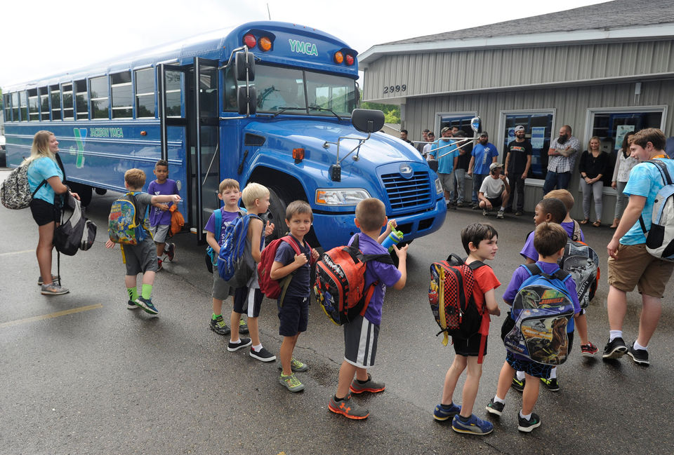 Students unload as two buses from the Jackson YMCA pull into Tripp's Auto Shop on Wednesday morning, June 27, 2018. The kids and other officials from the YMCA came to thank Tripp's and owners Phil and Barb Tripp for repainting and body work on the new buses. (J. Scott Park | MLive.com)